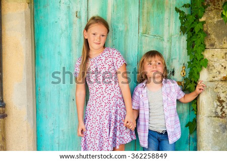 Summer portrait of two cute kids, young girl and her little brother standing against turquoise wooden old door  - stock photo