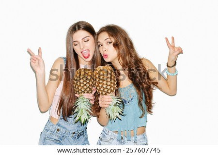 Summer portrait of two pretty brunette girl friends having fun with pineapple. Singing and smiling. Casual style, bright makeup, pink lips. White background, not isolated. Inside - stock photo