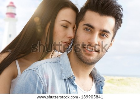Summer portrait of young attractive loving couple on the beach. - stock photo