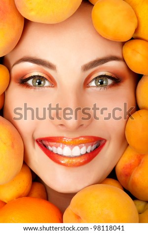 summer portrait of young healthy smiling attractive woman with ripe big fresh peaches and apricots - stock photo