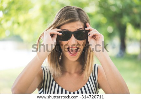 Summer portrait, young brunette woman playing with her sunglasses and having fun outdoor