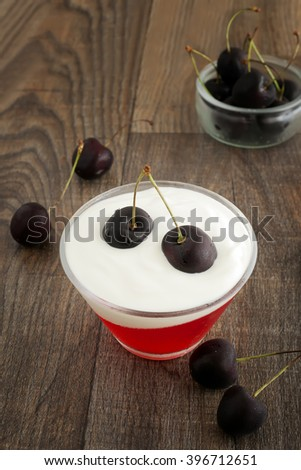 Summer refreshing dessert with black cherries, yogurt and red jelly. - stock photo