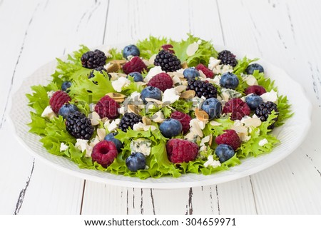 Summer refreshing mixed berry salad with pumpkin seeds, blue cheese, feta and almonds - stock photo