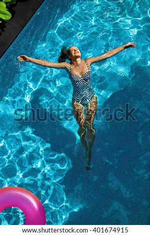 Summer Relax. Beautiful Carefree Happy Young Woman With Sexy Body In Swimsuit Having Fun With Colorful Float Swim Rings Floating In  Swimming Pool Water. Summertime Travel Holidays Vacation. Freshness
