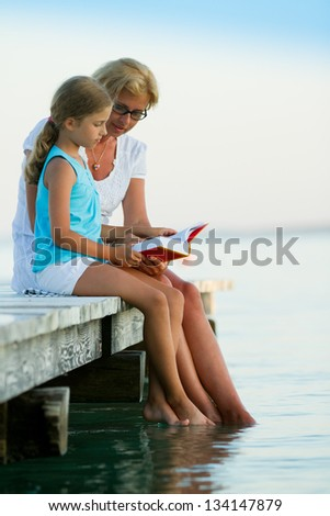 Summer relax, girl with mother reading a book on the pier - stock ...