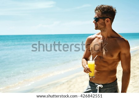 Summer Relax. Portrait Of Athletic Sexy Man With Muscular Body Drinking Fresh Juice Smoothie Cocktail On Tropical Beach. Handsome Fitness Male Model Sunbathing, Enjoying Refreshing Drink On Vacation - stock photo
