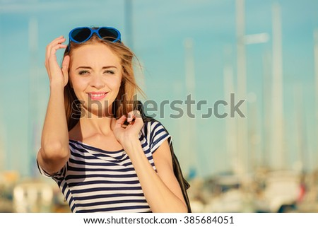 Summer relaxation concept.. Portrait girl with blue heart shaped sunglasses enjoying summer breeze outdoor in marina - stock photo