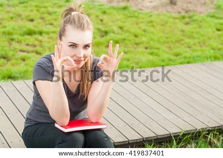 Summer relaxation with joyful female doing double ok gesture and holding a book in a spring sunny day with copyspace - stock photo