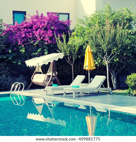 summer resort with outdoor furniture near the swimming pool in the beautiful garden, square vintage toned image, instagram effect  - stock photo
