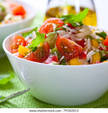 Summer rice salad with vegetables and fresh herbs - stock photo