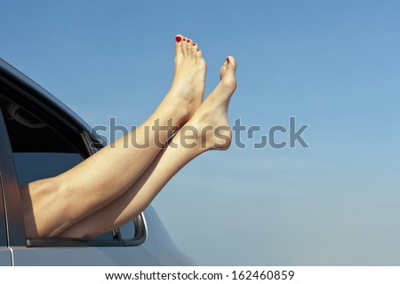 Summer road trip vacation concept. Woman's barefoot legs out the car window. Conceptual freedom, travel and holidays image with copy space. - stock photo