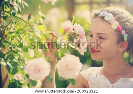 Summer, Rose garden - beautiful girl playing in the rose garden - stock photo