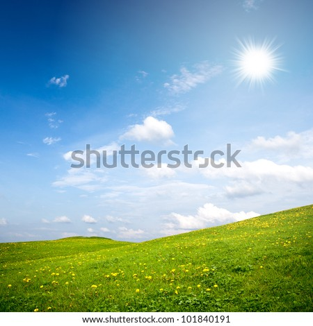 Summer rural landscape with green grass on hill and sunny blue sky - stock photo