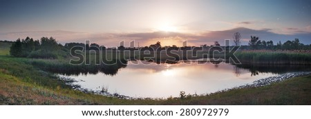 Summer rural landscape with river at dawn. Village on banks of river and beautiful rays of sun in sky. Panorama. Mirror reflection in water - stock photo