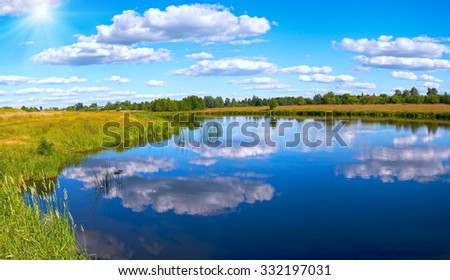 Summer rushy lake panorama view with clouds reflections and sunshine. - stock photo