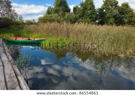 Summer's Russian lake scenery with wooden boat
