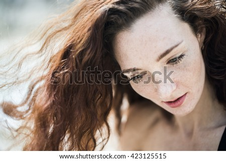 Summer sad portrait, beautiful freckled young adult girl with red hair look down. Cute curly redhead woman dreaming or thinking against outdoor background  - stock photo
