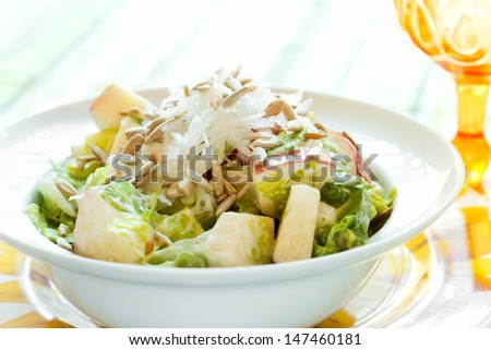 Summer salad with fresh crunchy apples and roasted raw sunflower seeds