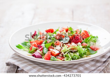 Summer salad with grapefruit, strawberry, mint, balsamico and cheese on a plate on a wooden background, closeup - stock photo