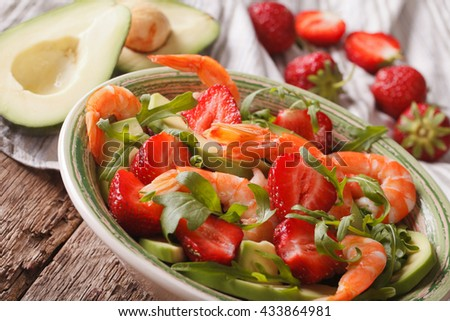 Summer salad with strawberries, avocado, shrimp and arugula close-up on a plate. horizontal