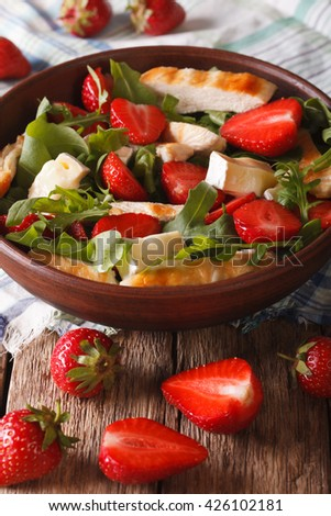 Summer salad with strawberries, grilled chicken, brie and arugula close-up on the table. vertical - stock photo