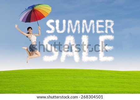 Summer sale clouds and woman jumping at meadow - stock photo
