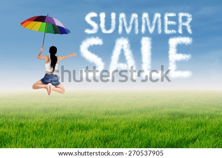 Summer sale clouds and woman jumping over green meadow - stock photo