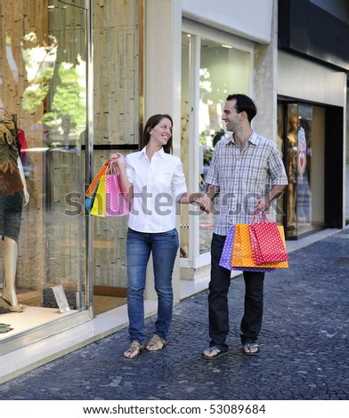 summer sale: couple with shopping bags in front of a store - stock photo