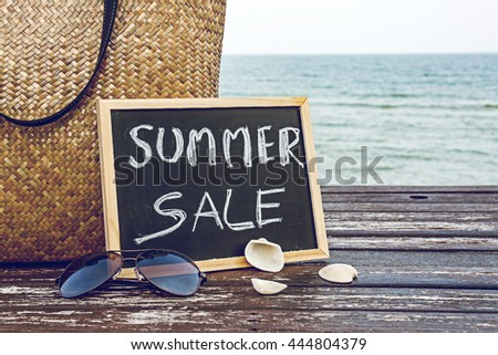 summer sale decorate with bamboo bag and chalkboard on wooden floor on the blue sea ,summer holiday travel and shopping concept. - stock photo
