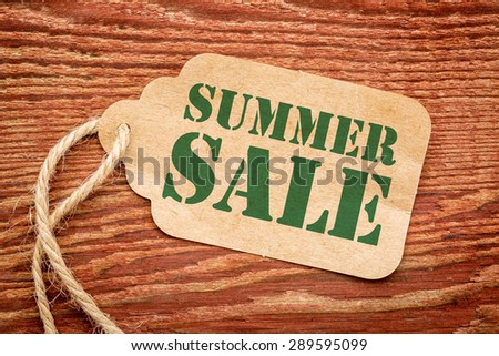 summer sale sign - a paper price tag against rustic red painted barn wood