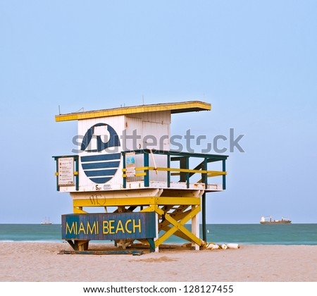 Summer scene in Miami Beach Florida, with a colorful lifeguard house in a typical Art Deco architecture, at sunset with blue sky in the background. Long exposure. - stock photo