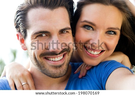 Summer scene of Happy young couple taking selfies with her smartphone in the park - stock photo