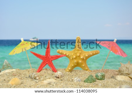 Summer scene #18 - Two star fishes with paper umbrellas - stock photo