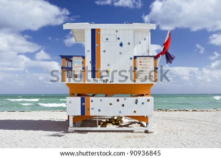 Summer scene with a landmark colorful lifeguard house in a typical Art Deco building style in Miami Beach, Florida with blue sky and ocean in the background. Back centered view. - stock photo