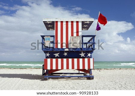 Summer scene with a lifeguard house in Miami Beach, Florida in the colors of the American flag with blue sky and ocean in the background. Back view.