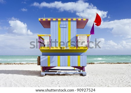Summer scene with a typical colorful lifeguard house in Art Deco style, typical for Miami Beach, Florida on a beautiful sunny day with blue sky and ocean in the background.