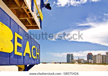 Summer scene with a typical colorful lifeguard house in Miami Beach, Florida with blue sky and skyscrapers in the background - stock photo
