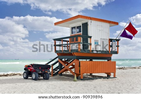 Summer scene with an orange colorful lifeguard house in a typical Art Deco style and a beach rescue car in Miami Beach, Florida with blue sky and ocean in the background. - stock photo