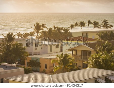 Summer scene with colorful buildings, palm trees, hotels and ocean in the background in Hollywood Beach, Florida bathing in golden light just after sunrise
