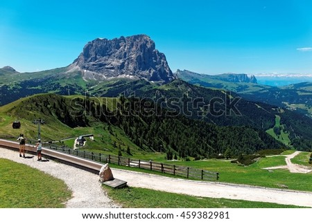 Summer scenery of rocky Mountains Sassolungo (Langkofel) & Schlern (Sciliar) with view of a cable car at mountainside & tourists on hiking trails in the valley in Selva di Val Gardena, Dolomiti, Italy