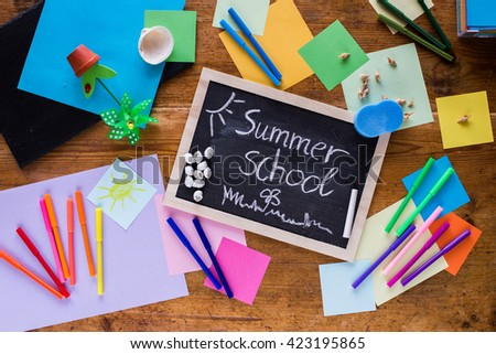 Summer school composition on a wooden table with a blackboard, chalk, colored papers and pens - stock photo