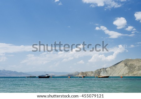 Summer sea resort. Blue sky with cumulus clouds. Sunny landscape with boats on the water. Mountains on the horizon - stock photo