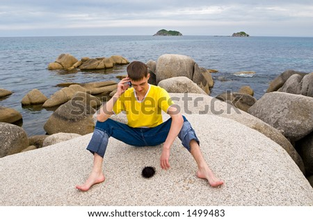 Summer.Sea.The young man speaks by mobile.On a stone the black sea-urchin lays. - stock photo