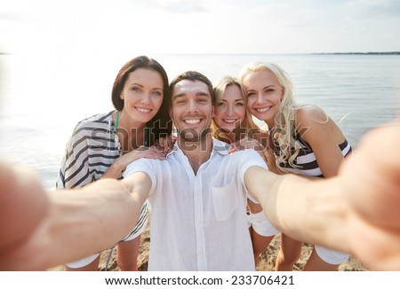 summer, sea, tourism, technology and people concept - group of smiling friends with camera on beach photographing and taking selfie - stock photo