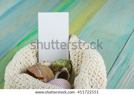 Summer sea vacation background with white blank business card Notebook blank page with Travel items on blue green wooden table. Sea shells, pebbles, top view mockup - stock photo