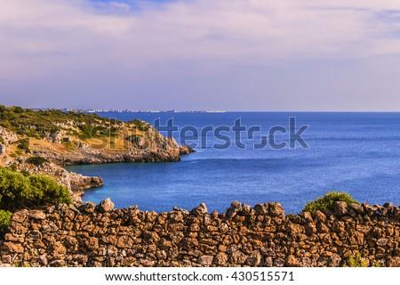 SUMMER SEASCAPE.Salento coast:Bay Uluzzo (Lecce).ITALY (Apulia).In the background the city of Gallipoli. Bay Uluzzo is a small natural gulf located within the protected area known as Porto Selvaggio. - stock photo