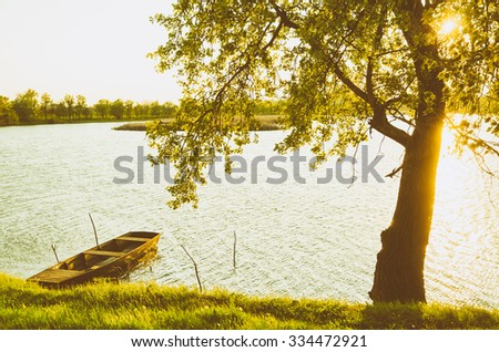 summer season landscape - wooden boat, backwater, tree and sunset. Warm calm weather.