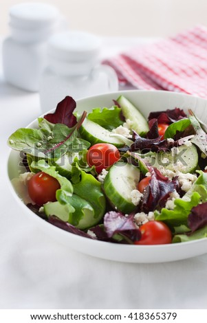Summer season salad with salad leaves, tomatoes, cucumbers, Italian herbs and cheese in a bowl on a table, closeup, selective focus  - stock photo