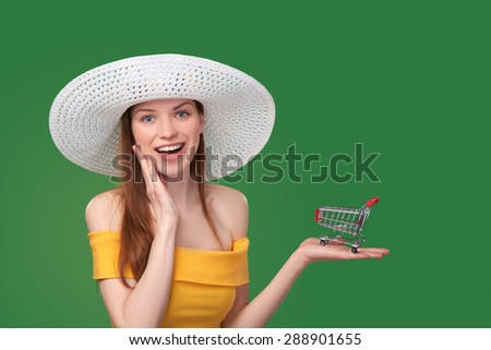 Summer shopping sale concept. Bright woman in yellow sundress and white hat showing small empty shopping cart - stock photo