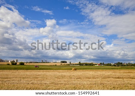 Summer sky over farm field with hay bales in Belarus - stock photo